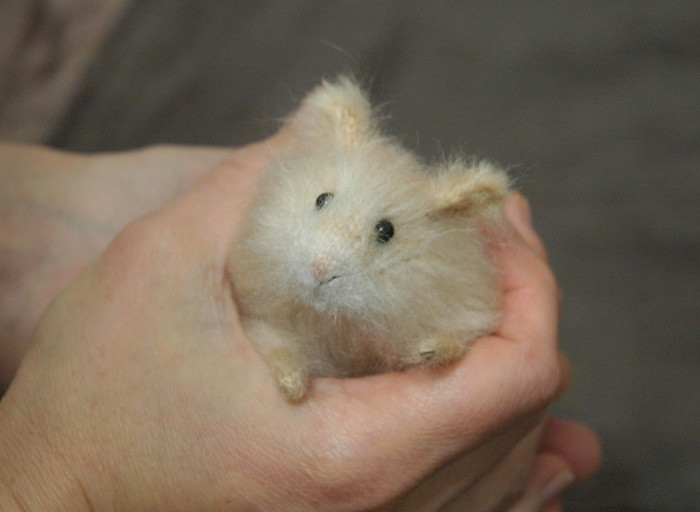 realistic hamster in hand
