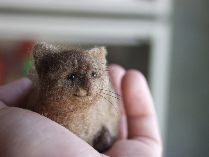miniature needle-felted cat held in hand